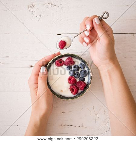 Closeup Of Young Woman Hands With A Bowl Of Yogurt. Girl Eating Organic Yogurt For Breakfast With Fr