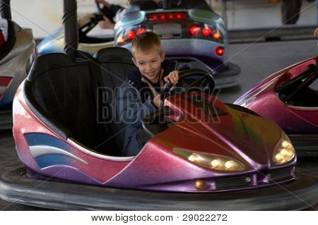 Boy driving an electric car in amusement park