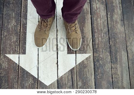White Arrow Sign On Wooden Floor. Mans Legs Standing On Arrow Sign Painted On The Floor. Direction S
