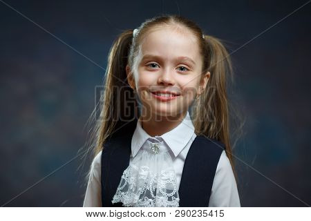 Smiling Caucasian Elementary Schoolgirl Portrait. Attractive Ponytail Girl Wear Nice Traditional School Uniform. Happy Child Look Positive Education System Concept Front Close-up Photo poster