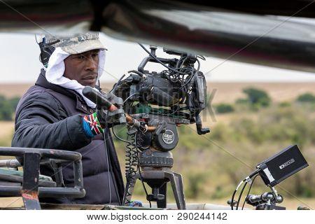 Masai Mara, Kenya - 10 August 2018: Nat Geo Wild cameraman prepares to film a wildebeest river crossing during the annual Great Migration in the Masai mara, Kenya.