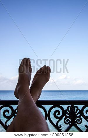 Legs on handrail with ocen and blue sky