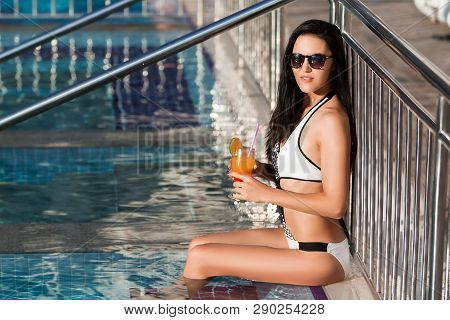 Pretty Young Slim Lady With Long Dark Hair Wearing A White Swim Suit Is Leaning On The Metal Fence O
