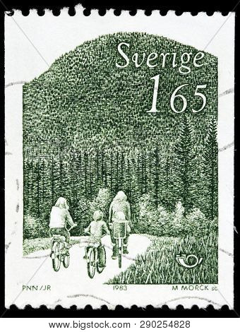 Luga, Russia - February 17, 2019: A Stamp Printed By Sweden Shows Cyclists Family Rides Bicycles Aga