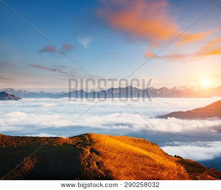 Morning view of the alpine valley in fog. Location place National Park Val Gardena, Seceda peak, Dolomiti, Tyrol, Italy, Europe. Landmark Val di Funes. Drone photography. Discover the beauty of earth.