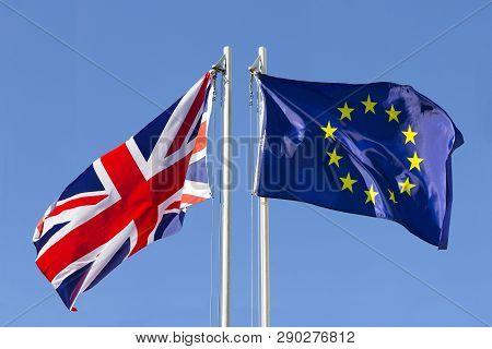 United Kingdom Flag Vs. European Union Flag On Flagpole In Front Of Blue Sky