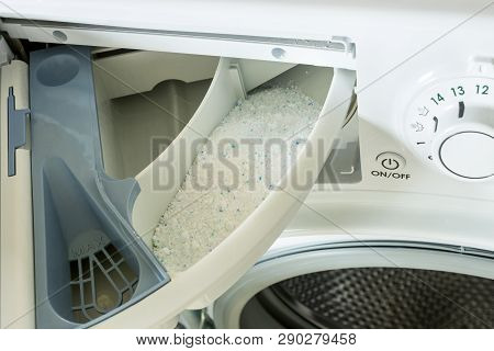 Detergent in the washing machine in laundromat. Concept- detergent dosage, housework, house cleaning. poster