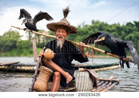 Yangshuo, China - July 27, 2018: Traditional Cormorant Fisherman On A Bamboo Rafts On Li River In Ya