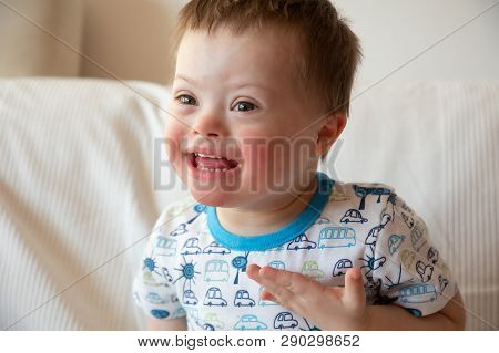 Portrait Of Cute Small Boy With Down Syndrome At Home