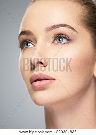 Beautiful face of young caucasian woman with perfect health clean skin.  Skin care treatment. Profile Portrait of an Attractive girl  with blue eyes, closeup.