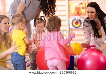 Mothers With Little Kids Doing Exercises With Red Gymnastic Ball At Gym. Concept Of Caring For The B