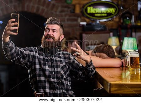 Take Selfie Photo To Remember Great Evening In Pub. Man Bearded Hipster Hold Smartphone. Taking Self