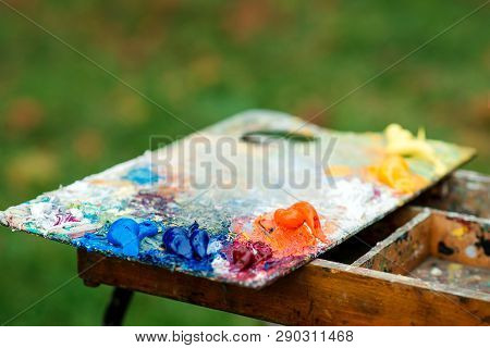 Art Palette On Nature Blured Background. Artist Paints A Picture Of Oil Paints. Dirty Art Palette. P