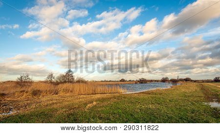 Picturesque Dutch Polder Landscape With White Clouds Against A Blue Sky. The Photo Was Taken In The
