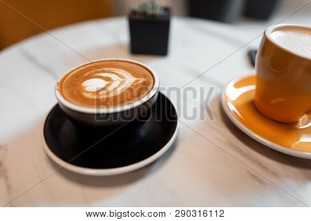 On The Table In The Cafe Is A Black Cup With A Hot Latte And A Yellow Mug With Cappuccino. Morning C