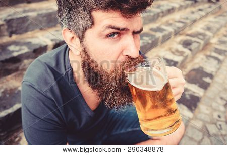 Guy Having Rest With Cold Draught Beer. Hipster On Calm Face Drinking Beer Outdoor. Man With Beard A