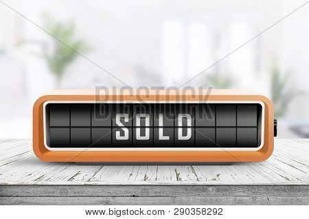 Sold Message On A Retro Alarm Clock In A Bright Room On A Wooden Table