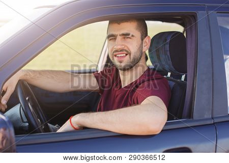 Handsome Young Dark Haired Male With Stubble Dressesd Maroon Casual T Shirt, Poses In Black Car, Loo
