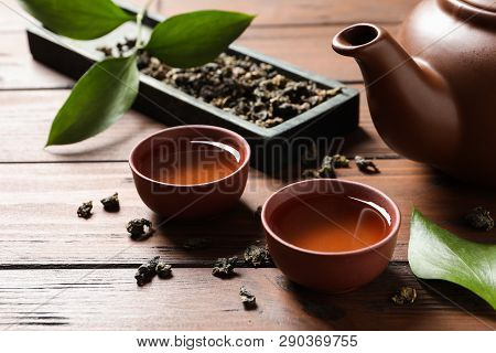 Cups And Teapot Of Tie Guan Yin Oolong On Wooden Table
