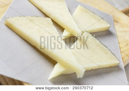 Manchego Cheese On Wooden Board With Olives