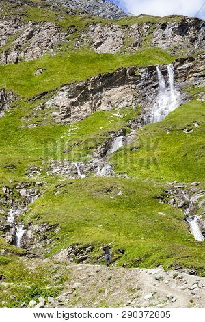 A Young Man In A Dub Dance Pose At Alpine Waterfall In Hohe Tauern National Park In Austria