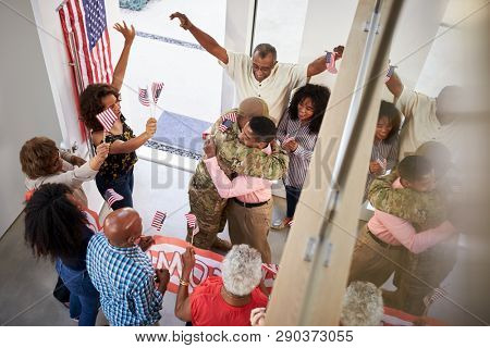 Young black male soldier welcomed home by three generation family, elevated view poster