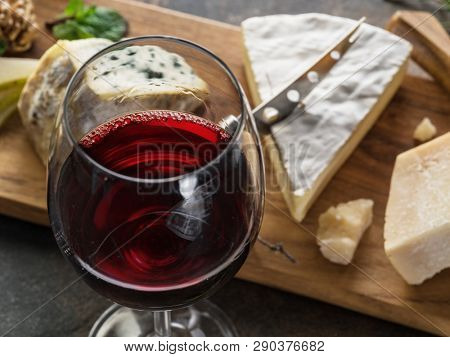 Cheese platter with blue cheeses, fruits, nuts and wine on stone background. Tasty cheese starter.