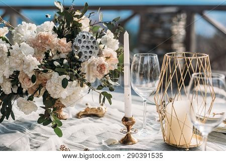 Luxury decorated table and wedding cake for a romantic date. Wedding details: tablecloth, candles, plates, glasses, near a mountain river on background. Wedding, calligraphy vintage