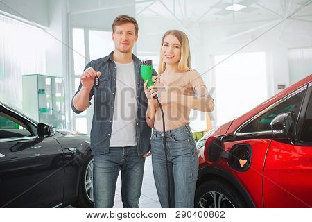 Young Smiling Family Buying First Electric Car In The Showroom. Environmental Protection. Attractive