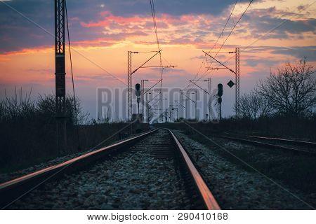 Sunset On The Railroad Tracks Landscape. Traveling By Train On Railroad In Sunset. Railroad Tracks L
