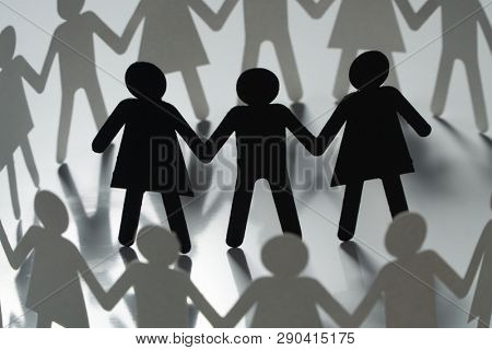 Three human paper figures surrounded by circle of paper people holding hands on white surface. Bulling, conflict, segregation concept.