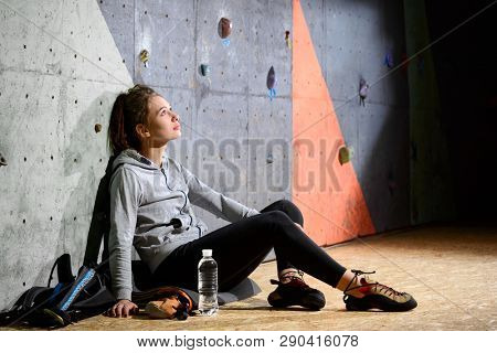 Young Active Woman Resting after Bouldering on the Colorful Artificial Rock in Climbing Gym. Extreme Sport and Indoor Climbing Concept