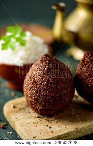 some kibbeh, a levantine dish, made of bulgur, onion, minced meat and different spices, on a rustic wooden table, with a bowl with rice and a golden teapot in the background