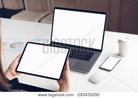 Woman Holding Tablet Screen Blank And Laptop On The Table Mock Up To Promote Your Products. Concept