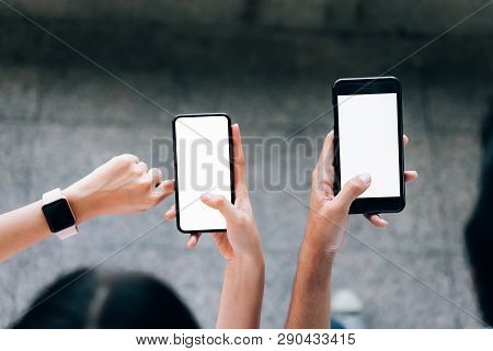 Woman And Man  Holding A Smartphone, Mock Up Of Blank Screen. Using Cell Phone On Lifestyle. Technol