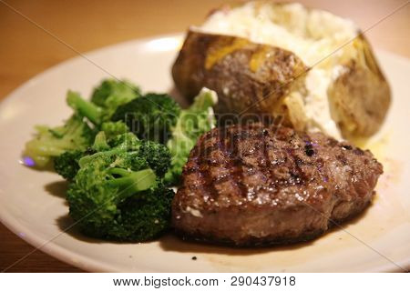 Steak and Potato dinner. Steak, Potato, Broccoli with cheese dinner on a white plate in a restaurant.  Dinner time