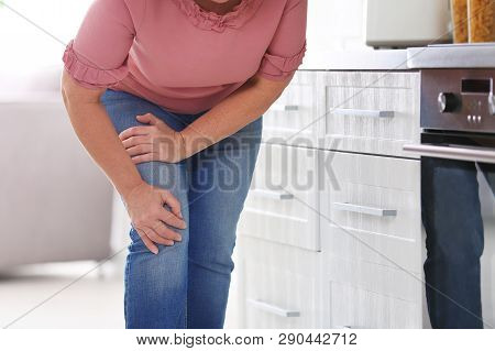 Senior Woman Suffering From Knee Pain In Kitchen, Closeup. Space For Text