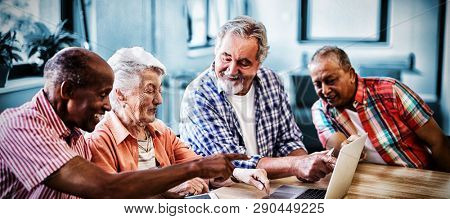 Happy senior men and woman using laptop while sitting at table in nursing home