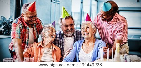 Cheerful friends looking at excited senior woman during birthday party in nursing home
