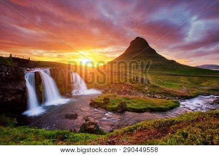 Majestic view of the awesome Kirkjufell volcano at sunset. Location place Kirkjufellsfoss waterfall, Iceland, Europe. Scenic image of most popular tourist attraction. Discover the beauty of earth.