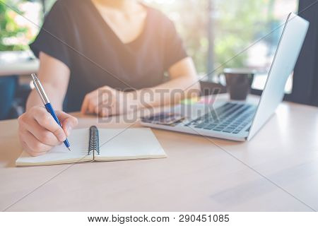 Woman Hand Is Writing On A Notepad With A Pen.on The Table, There Is A Laptop Computer And A Cup Of