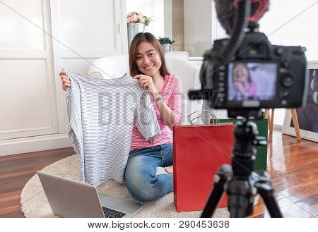 Asian Young Female Blogger Recording Vlog Video With Review Cloths T-shirt At Home Online Influencer