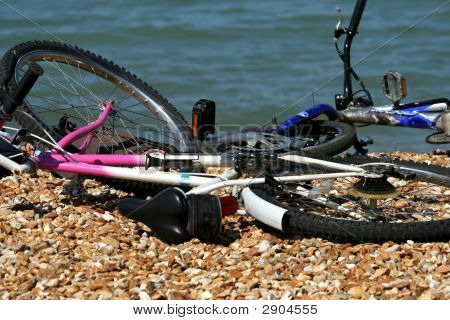 Kids Bikes Lying Around On The Pebbled Beach