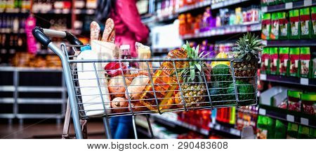 Various groceries in shopping cart in grocery section of supermarket