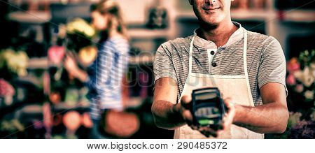 Portrait of florist showing credit card terminal in flower shop