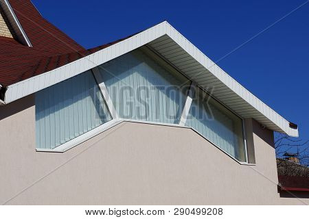 Large Window On The Gray Concrete Wall Of The Attic Under The Red Tile Roof Against The Blue Sky