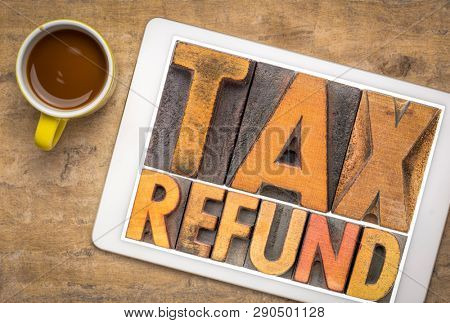 tax refund - word abstract in vintage letterpress printing blocks on a digital tablet with a cup of coffee against textured bark paper