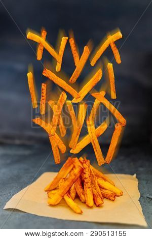 Homemade crispy Potato Fries with grain Salt flying ingredients. Fry delicious snack.