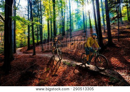 Cycling woman and man riding on bikes in  mountains landscape forest. Couple cycling MTB enduro trail track. Outdoor sport activity.