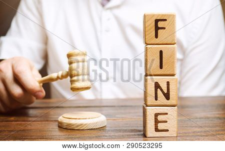 Wooden Blocks With The Word Fine And Judge. Penalty As A Punishment For A Crime And Offense. Financi